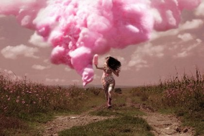 Girl running in a field in front of a pink cloud