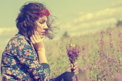 Girl sitting in a field with bouquet of wildflowers