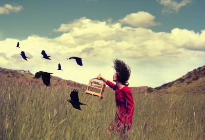 girl freeing birds from cage