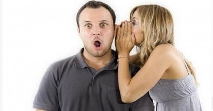 woman telling surprised man a secret