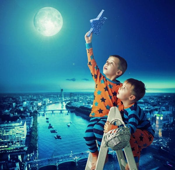 Two boys on a ladder trying to put a star in the night sky