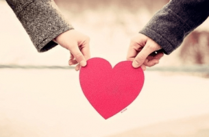 couple holding heart cut-out
