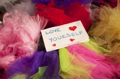 "Notecard reading ""Love Yourself"" among colored tissue paper"