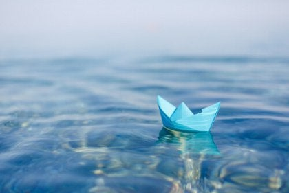 Small blue paper boat floating on water