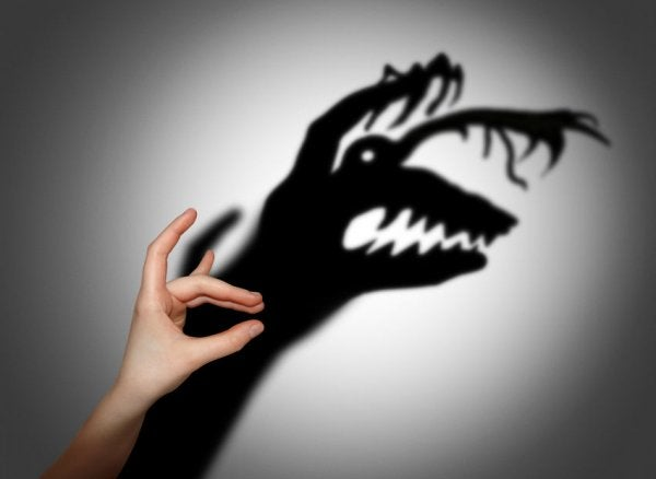 Hand making a shadow puppet that appears as an exaggerated monster