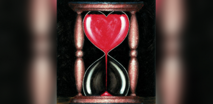 Hour glass shaped like heart with red sand