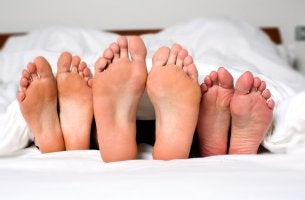 Three Sets of Feet in Bed