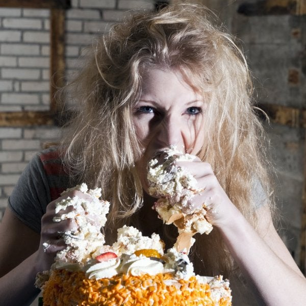 A woman eating sugary foods because she's stressed out.