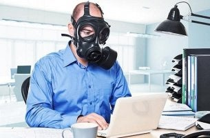 Man Wearing Gas Mask at Desk