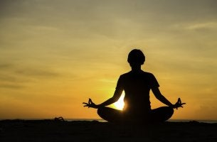 Person meditating with sunset behind