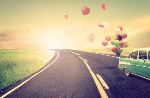 Open road, classic car towing balloons