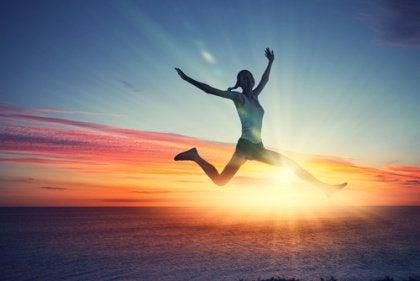 Girl Jumping, Sunset over Ocean