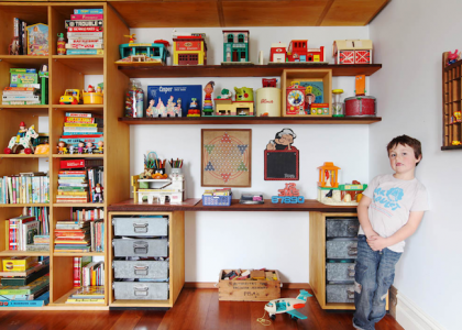 Boy in his room next to tall his toys