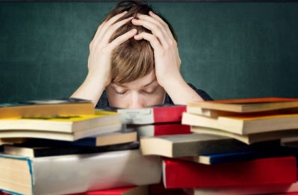 Boy Stressed Behind Books