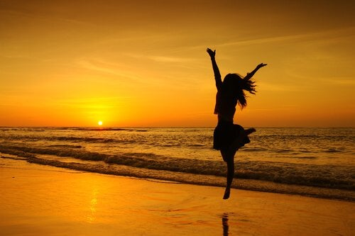 girl jumping on beach in sunset single