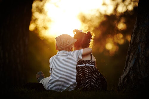 boy sitting hugging a girl at sundown