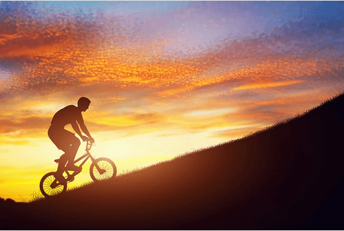 motivated man riding a bike up a mountain