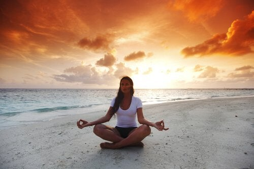 woman in lotus position on the beach meditating