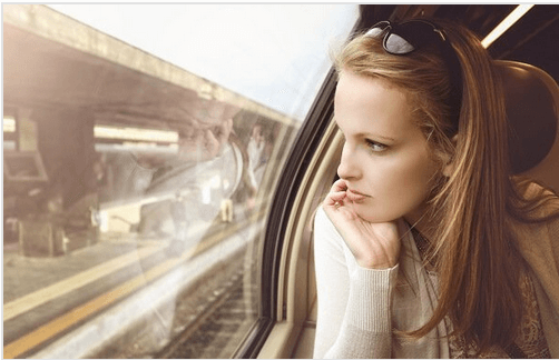 Tyttö katsoo ulos junan ikkunasta