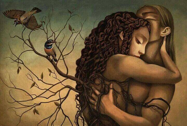 couple hugging in front of a tree with no leaves and birds