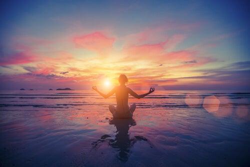Kvinne mediterer i solnedgangen
