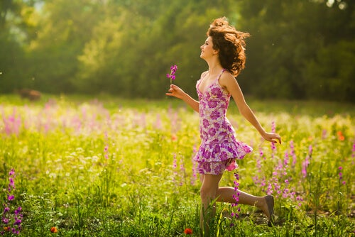 woman walking in flowers smiling and happy