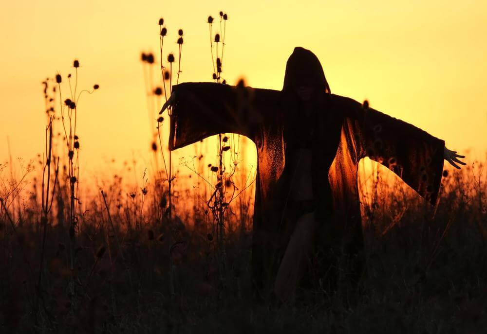 woman with cape at sunset