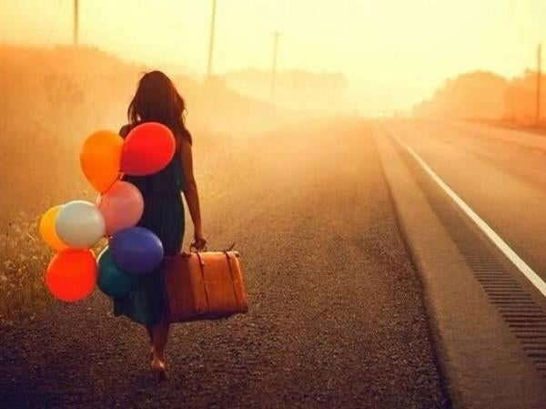 girl walking with balloons alive