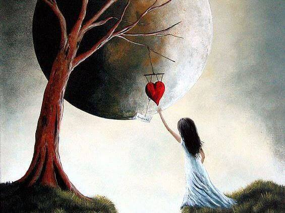 girl grabbing a heart hanging from a tree