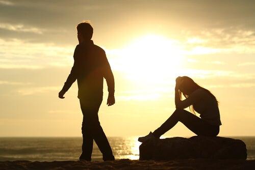 girl sitting on rock man walking on beach