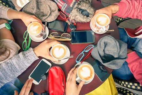 group of friends drinking coffee with cell phones on the table