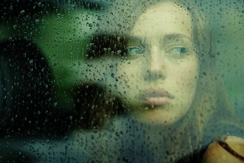woman looking through glass with droplets of rain