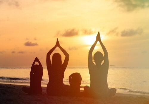 Perhe meditoi rannalla