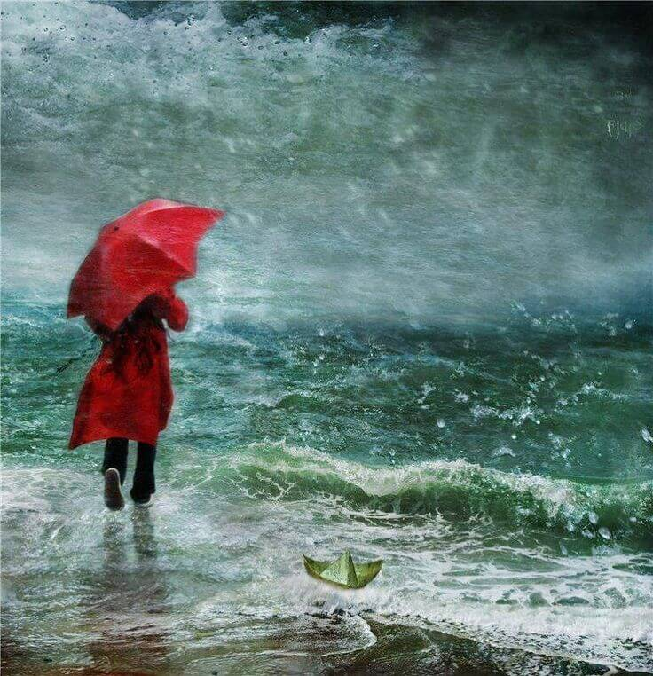 person walking into stormy sea