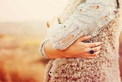 woman hugging self