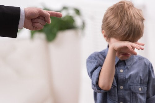boy crying being pointed at by his father