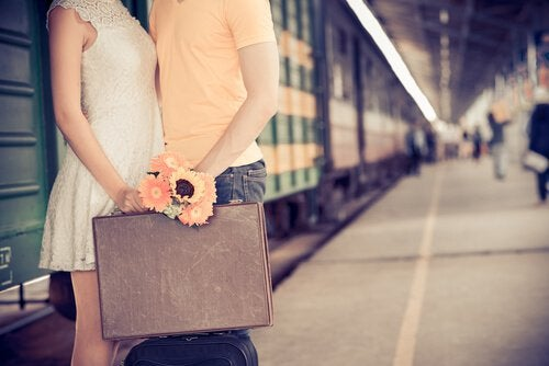 couple holding suitcase train station