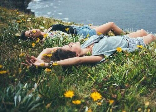 girls laying in field of flowers