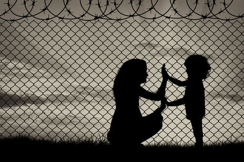 mother and daughter near a barbed wire fence