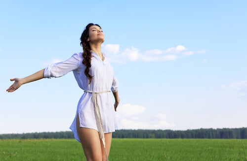 woman with open arms dressed in white in the field