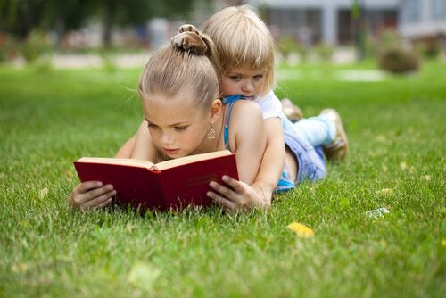 Siblings Reading Together on Grass