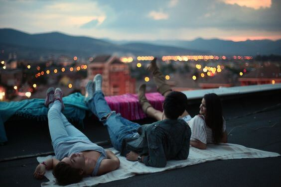Some friends on a roof at night.