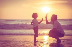 father and son high five at the beach