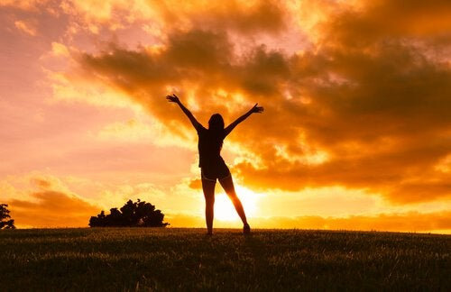 girl with arms stretched sunset
