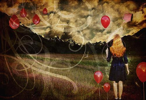 woman in a field holding balloons