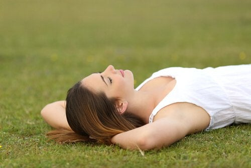 woman laying peacefully on grass