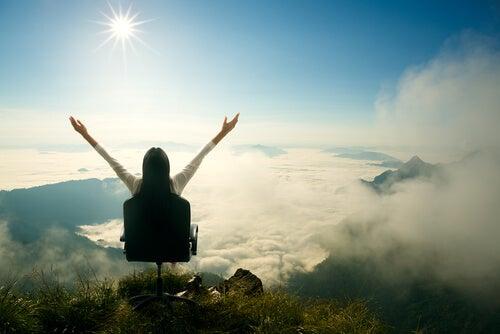 Kvinne har et lykkelig liv der hun sitter i en stol på toppen av et fjell