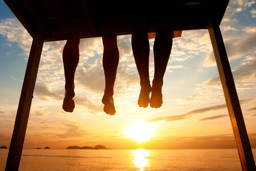 Friends Watching Sunset Legs Dangling