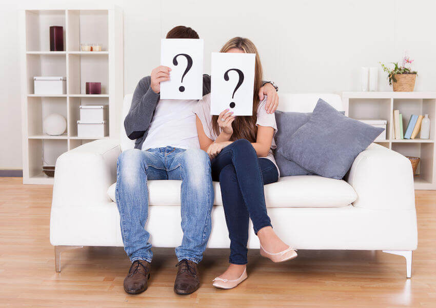 couple-holding-question-mark-signs