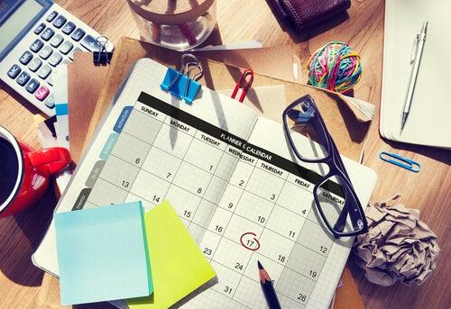 일과표, 안경, 노트가 있는 책상: 게으름을 극복하기 위한 방법